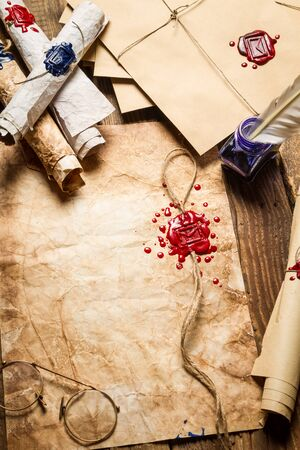 Old scrolls, sealing wax, old envelope and blue ink on wooden table Stock Photo - 19439824