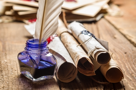Closeup of old scrolls and blue ink in the inkwell Stock Photo - 19439485