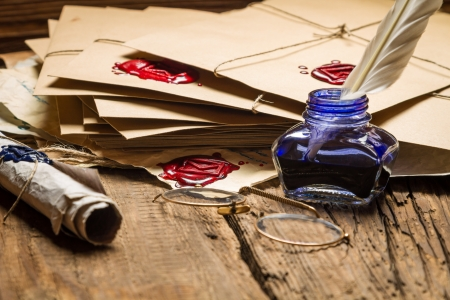 Closeup of blue inkwell and glasses on table filled with old messages Stock Photo - 19439483