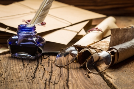Blue inkwell and glasses surrounded by ancient messages and envelopes Stock Photo - 19439473