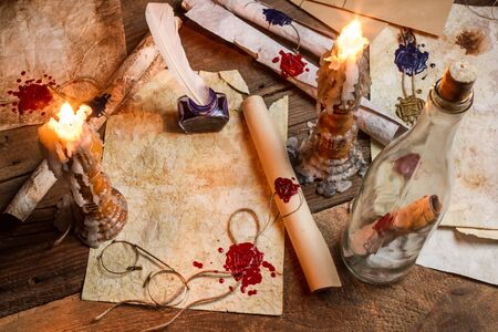 Antique table filled with old papers, red sealant and candles photo