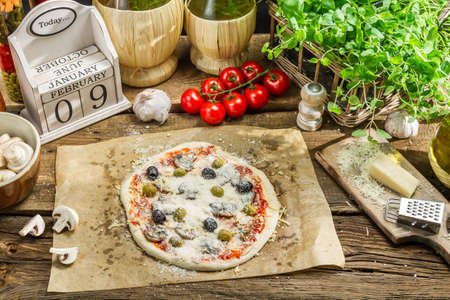 Prepared pizza with fresh ingredients ready to cooking photo