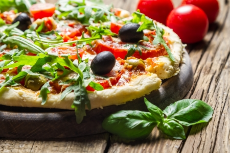 Closeup of freshly baked pizza with basil and tomatoes