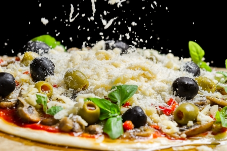 sprinkling: Falling cheese on a freshly prepared pizza on black background Stock Photo