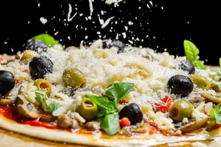 Vallende kaas op een vers bereide pizza op zwarte achtergrond