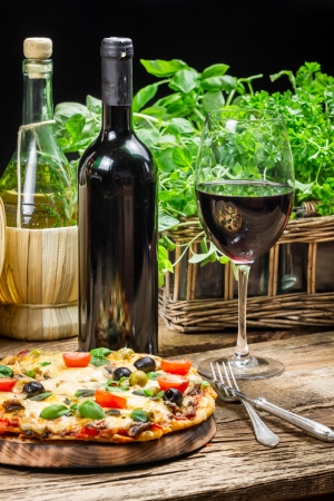 Freshly baked pizza served with red wine photo