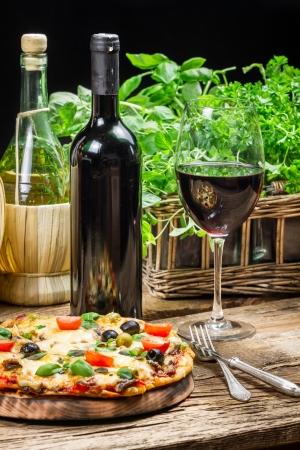 masa: Pizza recién horneado servido con vino tinto