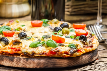 gourmet pizza: Closeup of freshly baked pizza served with wine Stock Photo