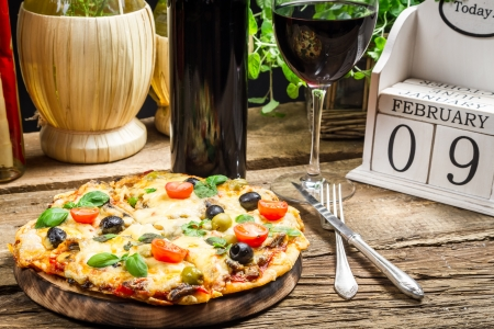 Freshly baked pizza served with wine on a calendar background Stock Photo