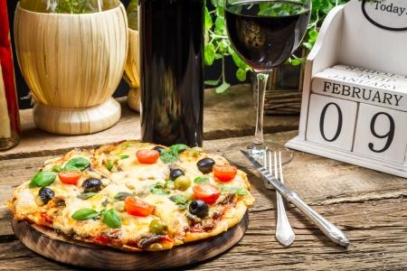 Frisch gebackene Pizza serviert mit Wein auf einem Kalender-Hintergrund