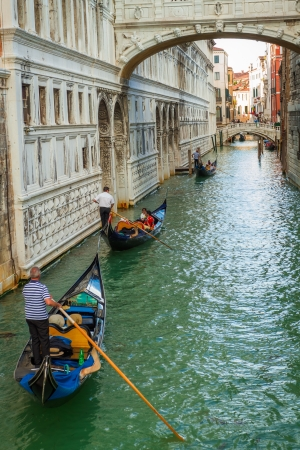 Gondoliers floating on a Grand Canal in Venice