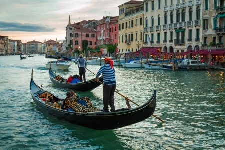 Gondoliers sailing with tourists on the Grand Canal at sunset in Venice