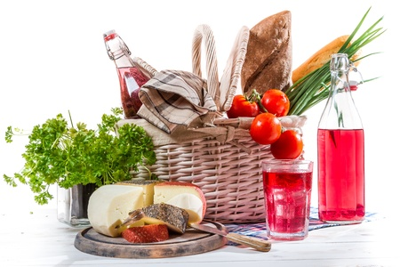 Picnic basket with vegetables and cheese photo