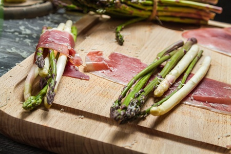 Preparation asparagus with prosciutto ham and cheese photo