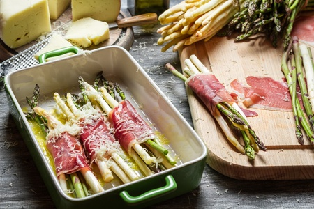 Preparation of asparagus wrapped in Parma ham with cheese photo