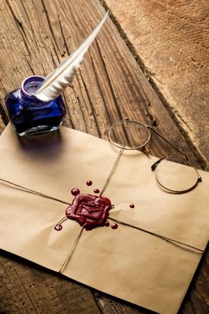 파란색 잉크의 잉크 병, 빨간 실란트와 봉투