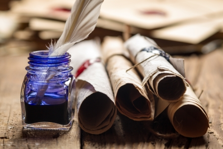 quill pen: Closeup of old scrolls and blue ink in the inkwell Stock Photo