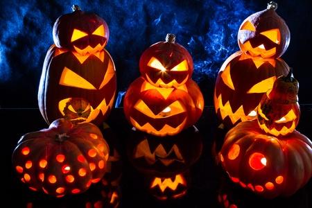 ugliness: Group strange halloween pumpkins on black background with smoke Stock Photo