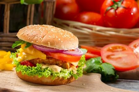 sandwich de pollo: Primer plano de una hamburguesa de pollo, tomate y verduras Foto de archivo
