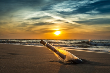 Ancient message in a bottle on a sea shore photo