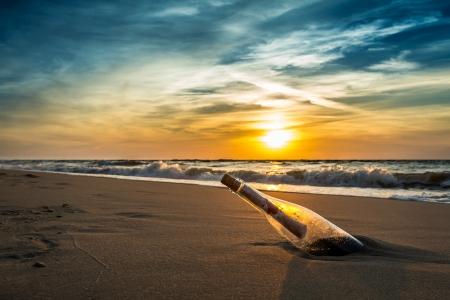 浜辺で夕日に対してボトルのメッセージ 写真素材