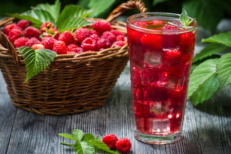 Juice of fresh raspberries served with ice in a glass photo