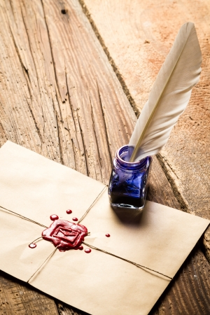Blue ink inkwell with feather on envelope with red sealant photo