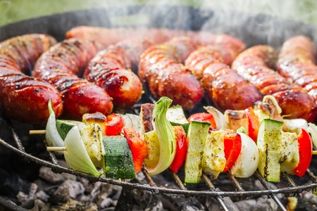 broiling: Closeup of sausages and skewers on the grill Stock Photo