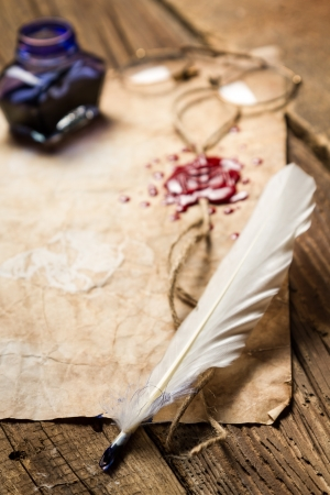 beeswaxseals: Closeup of a feather lying on vintage letter