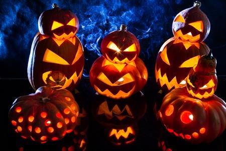 jack o latern: Group strange halloween pumpkins on black background with smoke Stock Photo