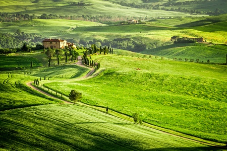 Sunset over farmhouse in Tuscany located on a hill photo
