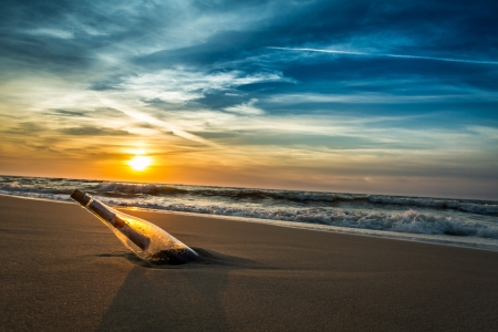 message in bottle: Message with letter inside the bottle on a beach in sunset Stock Photo