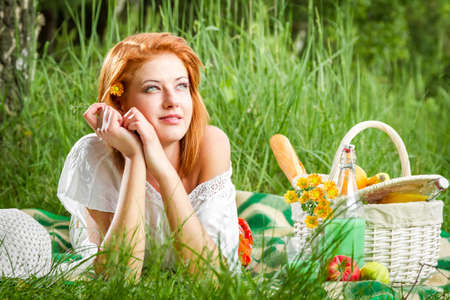 Dreamy young woman on picnic in summer photo