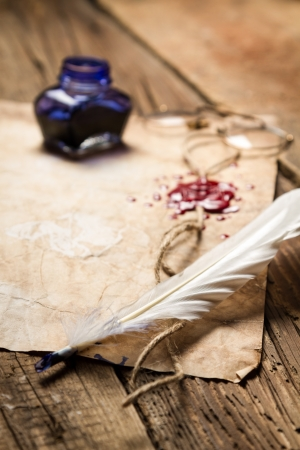 beeswaxseals: Closeup of a feather lying on old sheet of paper Stock Photo