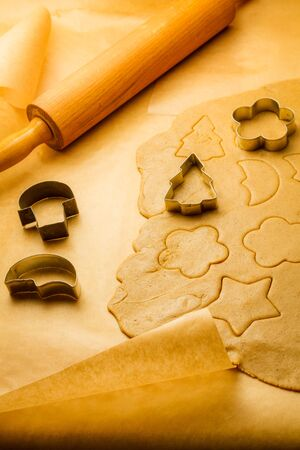 Cutting of different shapes of gingerbread cookies photo