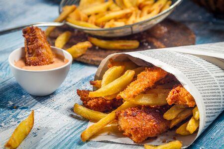 fish and chips: Gros plan des copeaux de poisson servi dans du papier