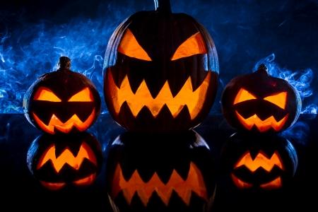 jack o latern: Three halloween pumpkins and blue smoke