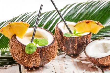 Pinacolada in a coconut on old white table photo