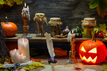 Pumpkin, old scrolls and candles in witch's cottage photo