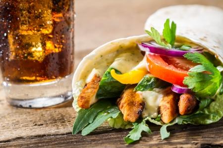 Närbild på kebab med färska grönsaker och kyckling på svart bakgrund