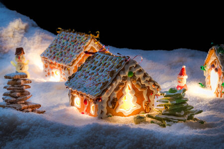Small gingerbread cottage in winter at night photo