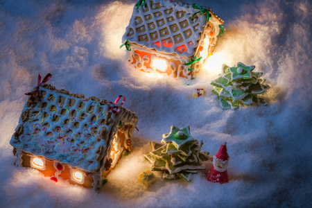 Snowy gingerbread cottage with santa and gifts photo