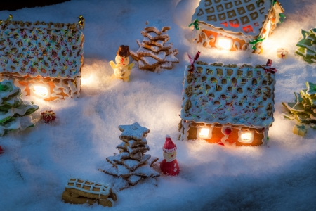 Snowy gingerbread village with santa, snowman and gifts