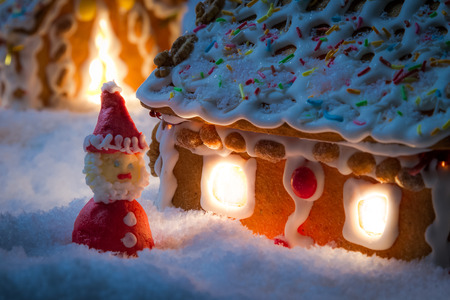 Closeup of marzipan santa near gingerbread cottage photo