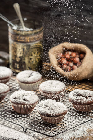 Icing sugar falling on fresh chocolate muffins photo