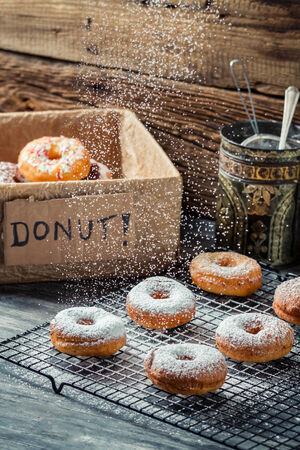 Closeup of falling powder sugar on fresh donuts photo