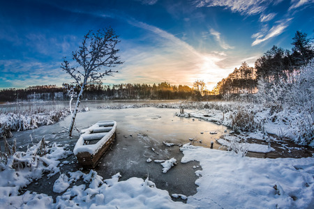 Frozen boat on the lake in winter at sunrise photo