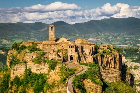 Forntida stad på kulle i Toscana på en berg bakgrund.