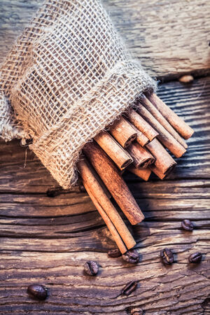 christmas scent: Cinnamon sticks in a burlap sack on the wooden table