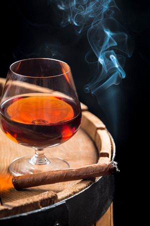 Smoking cigar and wooden brandy barrel photo